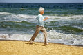 Elderly happy woman running on the beach along the coast near sea Royalty Free Stock Photo