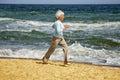Elderly happy woman running on the beach along the coast near sea Royalty Free Stock Photo
