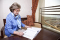 An elderly in her late s business woman sitting in a hotel s business lounge looking down at an empty page in a dossier holding a Stock Photography