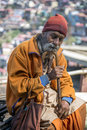 Elderly Indian beard man, face tilt down, wearing cultural rope and beads with walking stick. Royalty Free Stock Photo