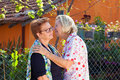 Elderly ladies greeting each other with a kiss on the cheek or leaning closing to whisper a secret or share the latest gossip as Royalty Free Stock Images