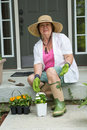 Elderly lady getting ready to transplant seedlings flower sitting on the steps of her porch in a sunhat gumboots and gloves with Stock Images
