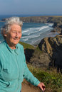 Elderly lady in her eighties with walking stick by beautiful coast scene with wind blowing through her hair at bedruthan steps Stock Photography