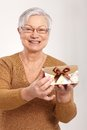 Elderly lady holding small present box smiling happy fancy Royalty Free Stock Photo