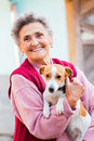 Elderly lady with pet happy holding her little dog outdoors in the garden Stock Photos