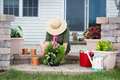 Elderly lady potting up new houseplants sitting on the steps of her patio in a wide brimmed sunhat transplanting seedlings into Royalty Free Stock Images