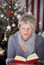 Elderly lady reading a book at christmas attractive stylish sitting in front of the decorated tree in her living room Stock Photos