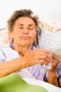 Elderly lady taking meds elder at home in bed Stock Photos