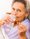 Elderly lady taking meds elder at home in bed Royalty Free Stock Photo