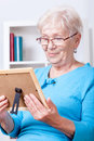 Elderly lady viewing family picture Royalty Free Stock Image