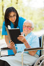 Elderly lady in wheelchair reading senior outdoors bible with nurse Royalty Free Stock Image