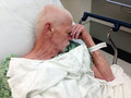 Elderly male hospital patient in hospital bed an man a resting his head on his hand wearing a gown and covered with a sheet he has Stock Photos
