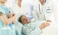 Elderly male patient lying in hospital bed wearing pyjama medical team around Royalty Free Stock Photography