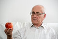 Elderly man with apple holding an in his hand Royalty Free Stock Images