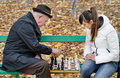 Elderly man arguing during a game of chess with woman sit together on a wooden park bench men women surrounded by fallen autumn Royalty Free Stock Photo