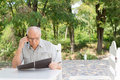 Elderly man chatting on his mobile phone sitting outdoors and reading a menu at an open air restaurant Royalty Free Stock Photo