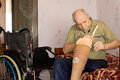 Elderly man checking out his artificial leg handicapped as he attaches the electronic sensors to the prosthesis before fitting it Stock Photos