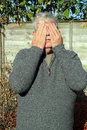 Elderly man covering eyes with his hands an two so that he can not see Royalty Free Stock Photo