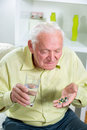 Elderly man drinking pills and water in the living room Stock Images