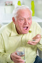Elderly man drinking pills and water in the living room Royalty Free Stock Photo