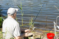 Elderly man enjoying a days fishing on lagoon or lake sitting with his back to the camera holding rod and reel Royalty Free Stock Photography