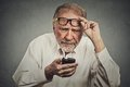Elderly man with glasses having trouble seeing cell phone closeup portrait headshot has vision problems bad text message negative Royalty Free Stock Image