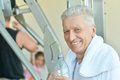 Elderly man in a gym drinking water after exercise Stock Photo