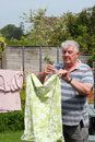 Elderly man hanging out the washing. Royalty Free Stock Photo