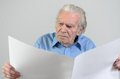 Elderly man holding a blank big white paper sheet Royalty Free Stock Photo