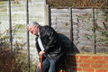 An elderly man leaning against a wall holding a walking stick and feeling ill in pain and bent over Stock Images