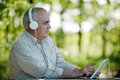 Elderly man listening to music on a tablet computer sitting relaxing under shady trees in the park selecting tune the Stock Photos