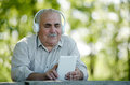 Elderly man listening to online music sitting at a table in the park searching his tablet for a tune as he listens his Stock Photography
