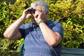 Elderly man looking through binoculars. Royalty Free Stock Photo