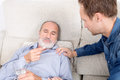 Elderly man looking at a pill sick senior lying in bed with help his side Stock Photo