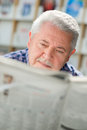 Elderly man with mustache reading paper in library Royalty Free Stock Photo