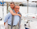Elderly man piggybacking his wife on a sailboat Stock Photos