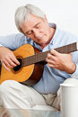 Elderly man playing guitar Royalty Free Stock Image