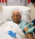 Elderly man plus year old recovering from surgery in a hospital bed Stock Photos