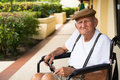 Elderly man plus year old in a wheel chair outdoors Stock Photos