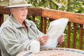 Elderly man reading newspaper and drinking coffee senior white male sitting outside on patio Royalty Free Stock Image