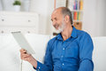 Elderly man reading the screen of his tablet pc relaxing on a sofa at home and smiling with pleasure in enjoyment Royalty Free Stock Photo