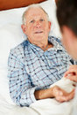 Elderly man receiving pill from the doctor Stock Photo