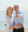 Elderly man showing something hand an woman on the beach happy men women Stock Photo