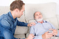 Elderly man sich at home sick senior lying in bed with help his side Stock Images