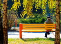 An elderly man sitting on a bench in autumn park. Royalty Free Stock Photo