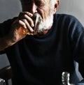 Elderly man sitting drinking whiskey alcoholic addiction bad habit Royalty Free Stock Photo