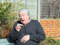 Elderly man sitting outside sneezing cold Stock Photo