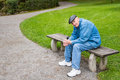 Elderly man sitting on park bench senior male in jeans resting a copy space Royalty Free Stock Photos