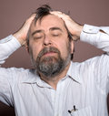 Elderly man suffering from a headache and holding his head by hands Stock Image