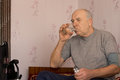 Elderly man taking his medication drinking the tablets down with a glass of water Stock Images